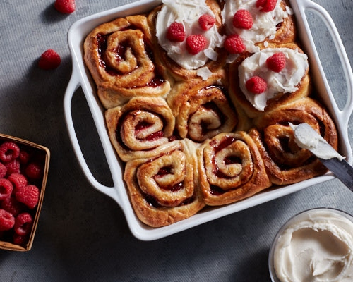 Fresh vegan raspberry cinnamon rolls in a baking dish, some bare, some with coconut glaze and raspberries