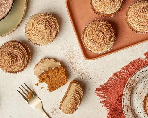 Pumpkin spice cupcakes with frosting, one cut in half, on a table