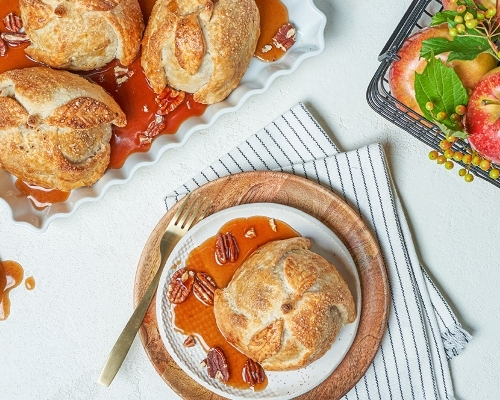 Three apple dumplings on a tray with apple cider syrup, and one on a plate