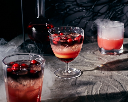 Black vodka and cranberry cocktail on a spooky background with swirling smoke