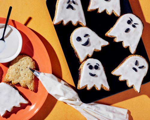 Ghost-shaped tarts, some decorated with black icing faces drawn on white icing, some undecorated