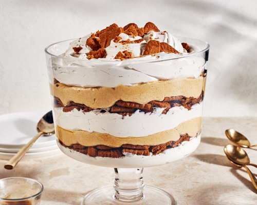 Family-size pumpkin cheesecake trifle in a large, stemmed glass bowl with cookie crumble on top
