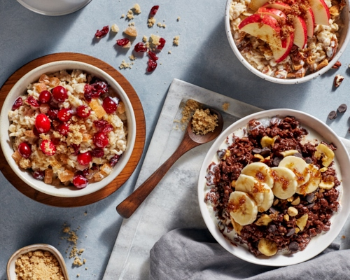 Three bowls of homemade oatmeal with brown sugar, fruit, and berries