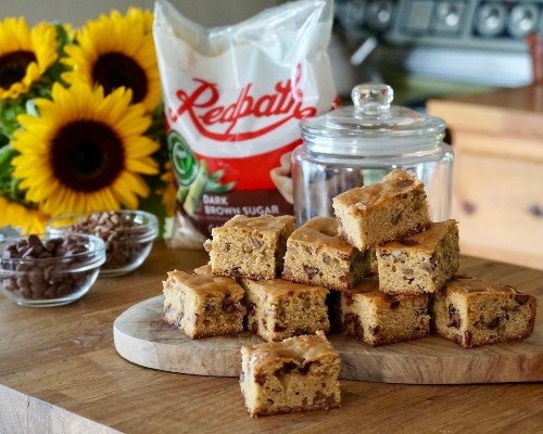 Brown Butter Blondies with chocolate chips on a butcher block counter with sunflowers and a bag of Redpath Dark Brown Sugar