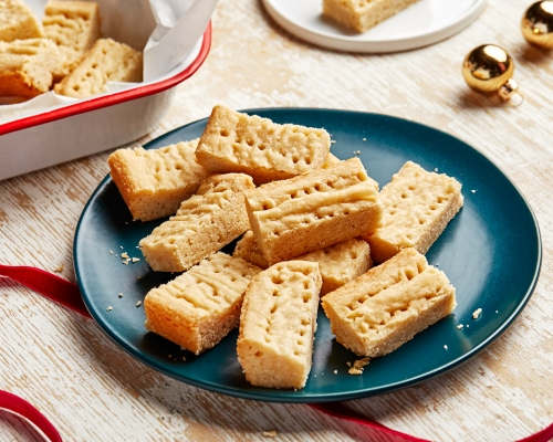Shortbread cookies on a blue plate with red ribbons and gold Christmas ornaments
