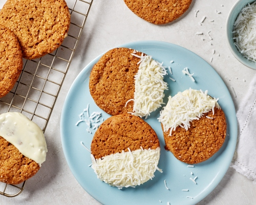 Gingersnap cookies half dipped in white chocolate and coconut on a blue plate and a wire cooling rack