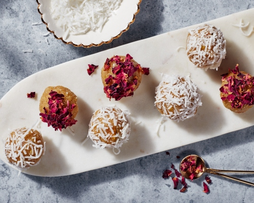 Golden Badam Ladoo garnished with rose petals and coconut on a thin white platter